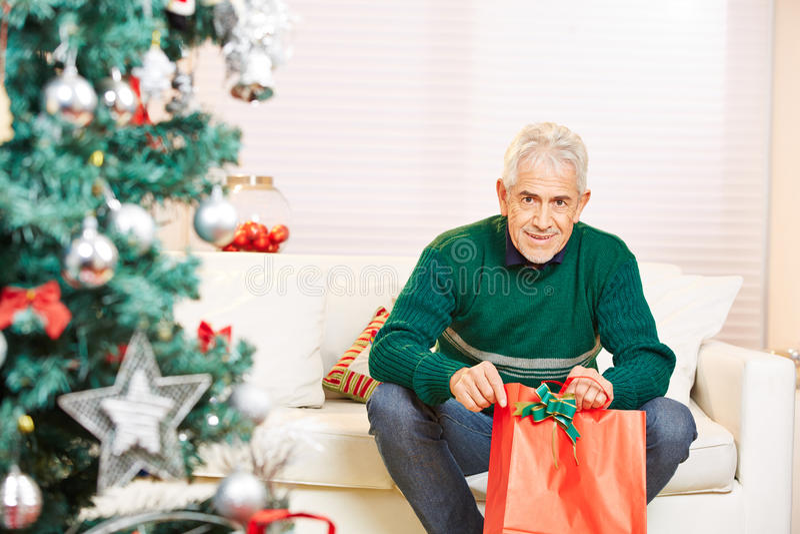 Starszy mężczyzna z prezentem przy bożymi narodzeniami obrazy royalty free