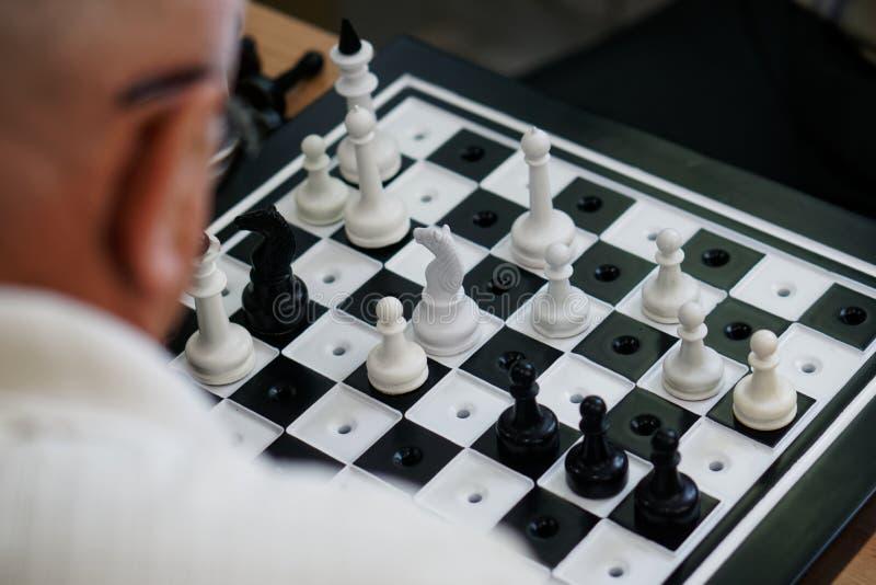 Starszy m??czyzna z szk?ami bawi? si? specjalnego szachy dla story fotografia stock