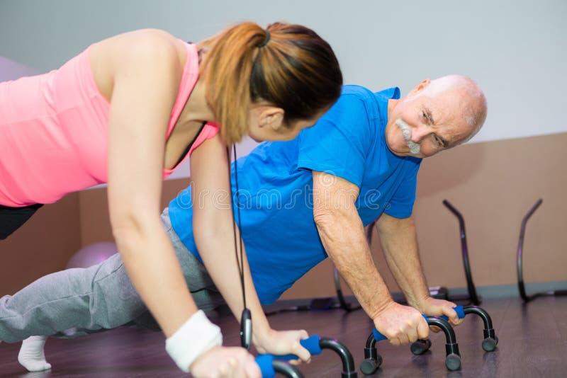 Starszy mężczyzna z uśmiechniętym żeńskim sprawność fizyczna trenerem zdjęcia stock