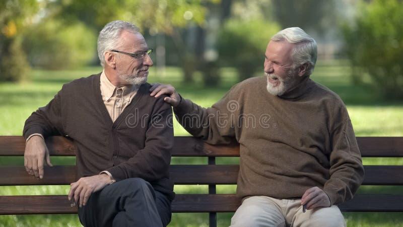 Starszy męscy przyjaciele dymi cygaro, przyjaciele cieszy się odpoczynek w parku wpólnie zdjęcie stock