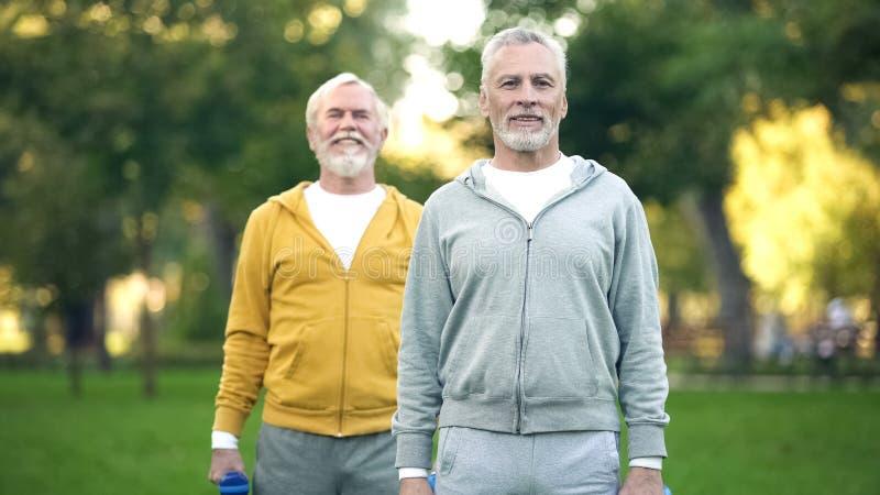 Starszy męscy przyjaciele trenuje w parku, pompuje mięśnie podnosi dumbbells, zdrowie fotografia stock