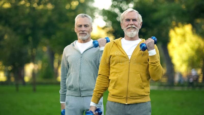Starszy m??czy?ni podnosi dumbbells w parku, przyjaciele opracowywa wp?lnie, sprawno?? fizyczna zdjęcia royalty free