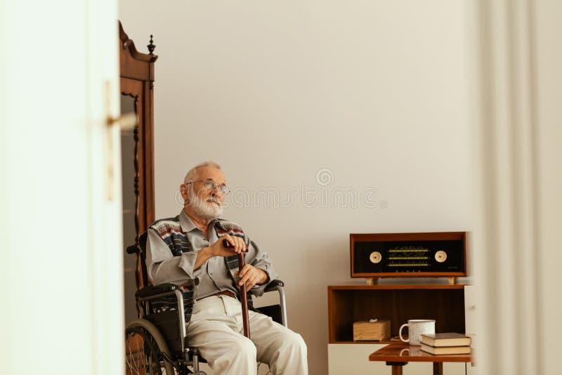 Starszy m??czyzna z chodz?cego kija obsiadaniem na karle samotnie w jego mieszkaniu i z popielatym w?osy i brod? fotografia stock