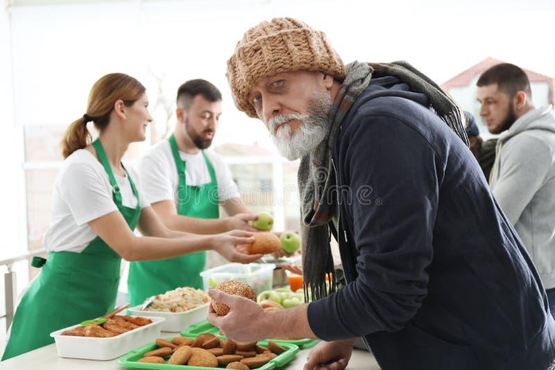 Starszy m??czyzna z innymi biednymi lud?mi otrzymywa jedzenie od wolontariusz?w obraz stock
