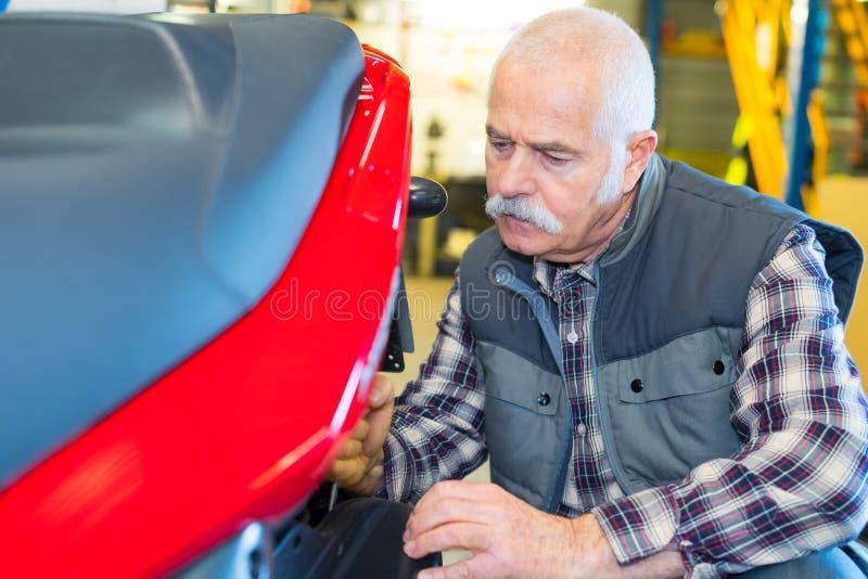 Starszy mechanik pracuje na nowożytnej hulajnodze obraz stock