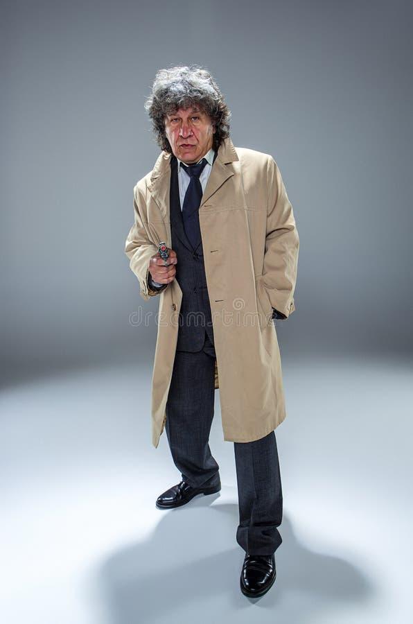 Starszy milicyjny agent z pistoletem na pracownianym tle fotografia stock
