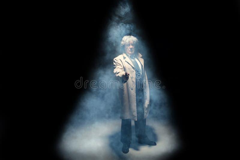 Starszy milicyjny agent z pistoletem na zmroku dymu tle fotografia royalty free