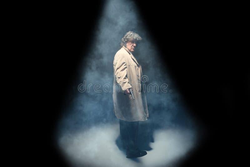 Starszy milicyjny agent z pistoletem na zmroku dymu tle zdjęcia royalty free