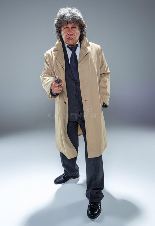 Starszy milicyjny agent z pistoletem na zmroku dymu tle zdjęcia stock