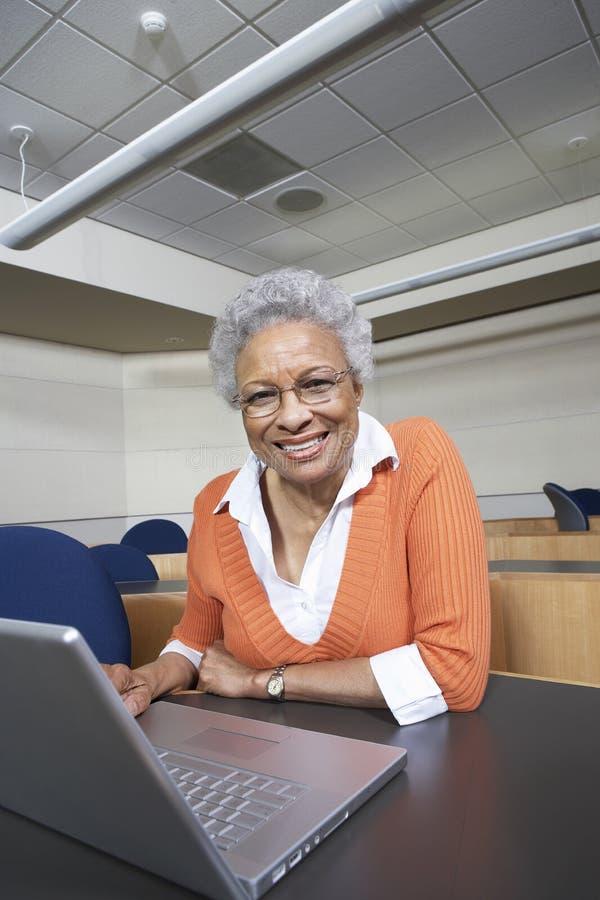 Starszy nauczyciel Używa laptop Przy biurkiem zdjęcie royalty free