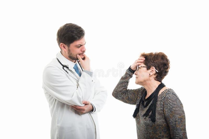 Starszy pacjenta i samiec doktorski robi rozwiązywanie problemów gestykuluje zdjęcia stock