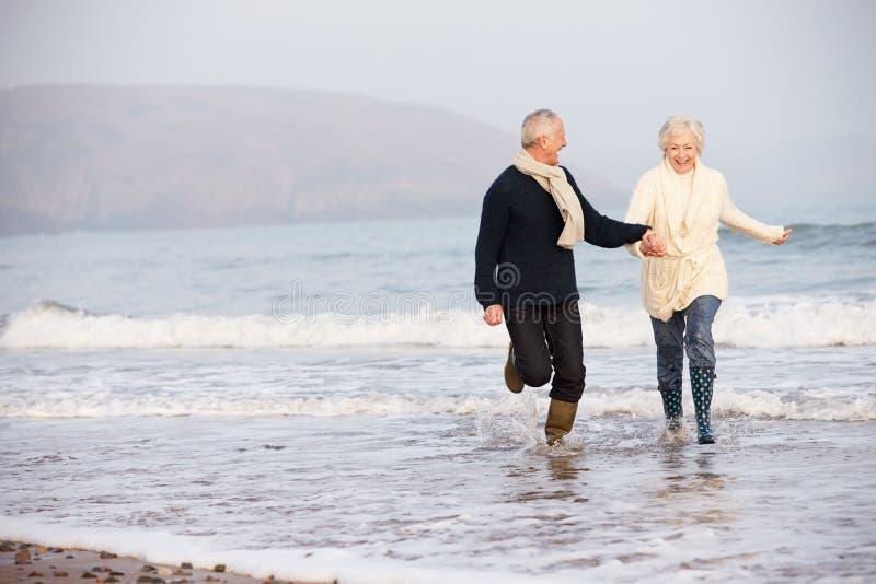 Starszy para bieg Wzdłuż zimy plaży fotografia stock