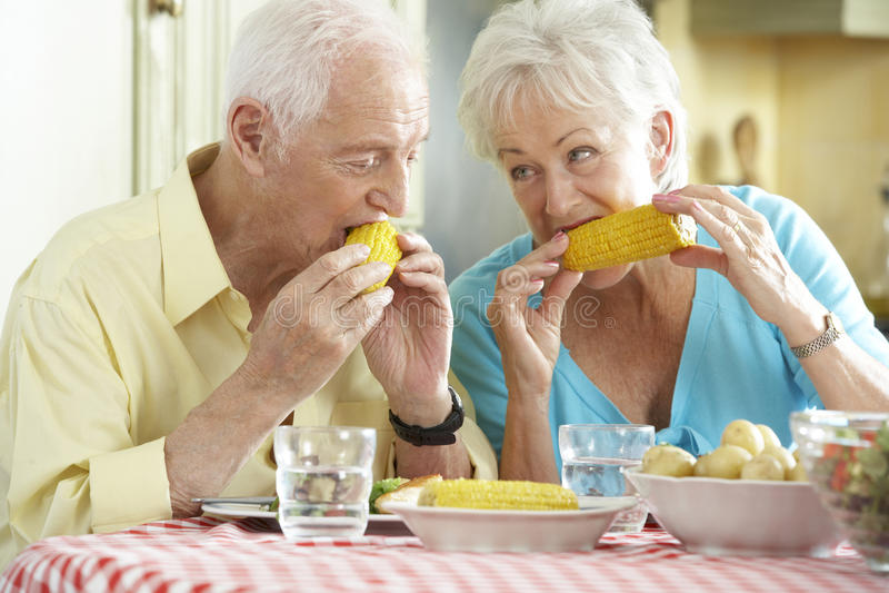 Starszy pary łasowania posiłek Wpólnie W kuchni fotografia royalty free