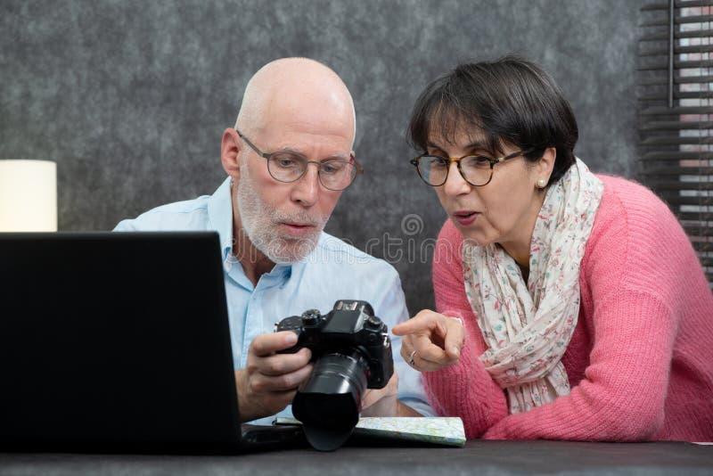 Starszy pary dopatrywania wakacje obrazki na kamerze fotografia royalty free
