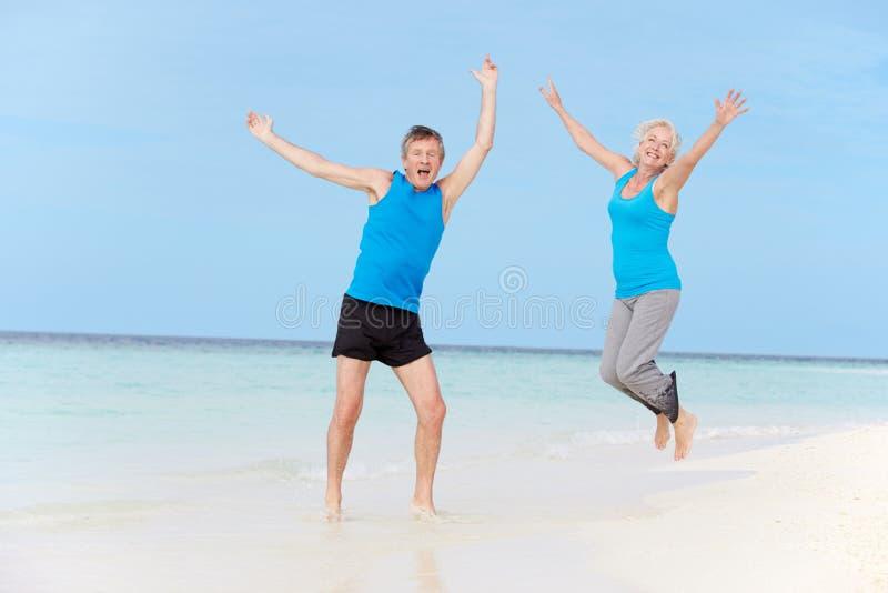 Starszy pary doskakiwanie Na Pięknej plaży zdjęcie stock