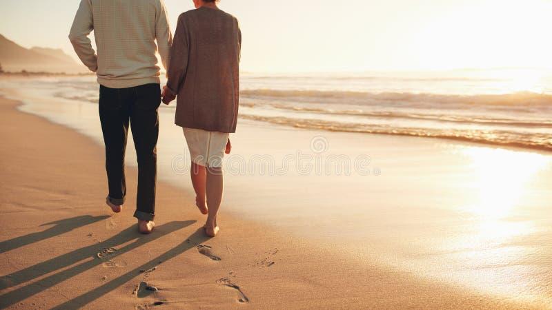 Starszy pary mienie wręcza odprowadzenie na plaży fotografia royalty free