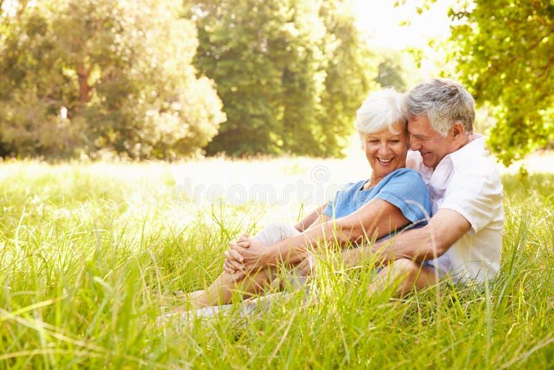 Starszy pary obsiadanie na trawie wpólnie relaksuje obrazy royalty free