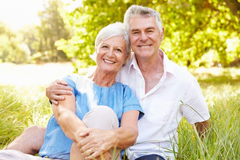 Starszy pary obsiadanie na trawie wpólnie relaksuje zdjęcia stock