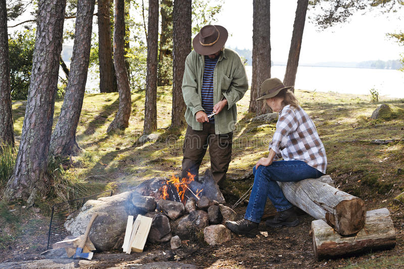 Starszy pary obsiadanie obozowym ogieniem obok jeziora obraz royalty free