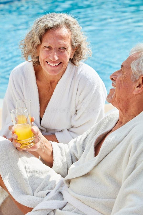 Starszy pary obsiadanie relaksujący basenem zdjęcie stock