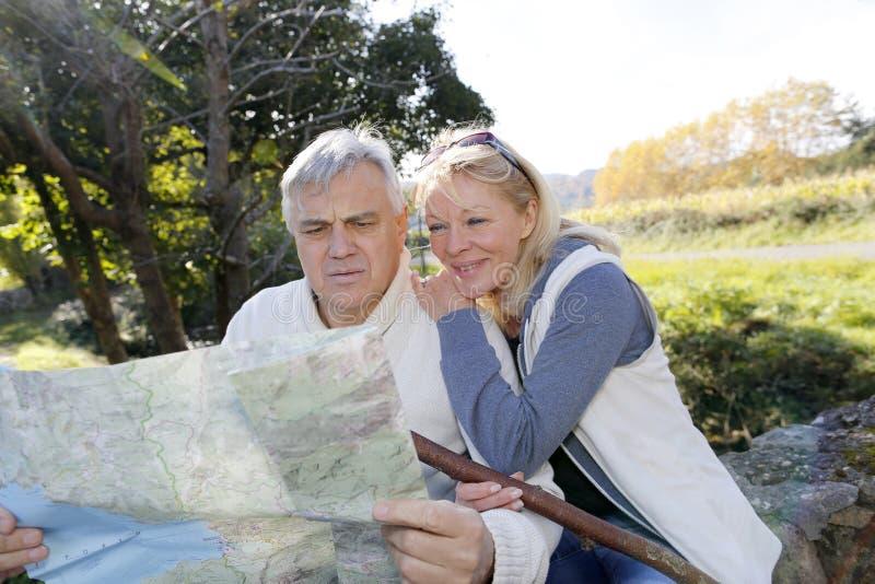 Starszy pary obsiadanie rzeczną patrzeje mapą zdjęcie royalty free