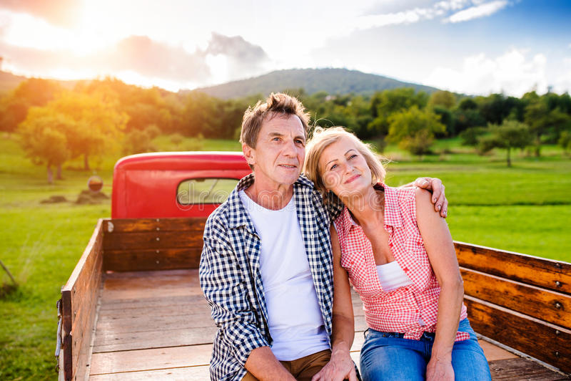 Starszy pary obsiadanie w plecy czerwona furgonetka zdjęcia royalty free