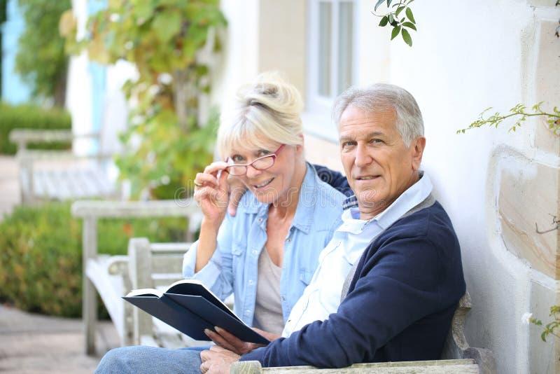 Starszy pary obsiadanie w podwórka czytaniu zdjęcie stock
