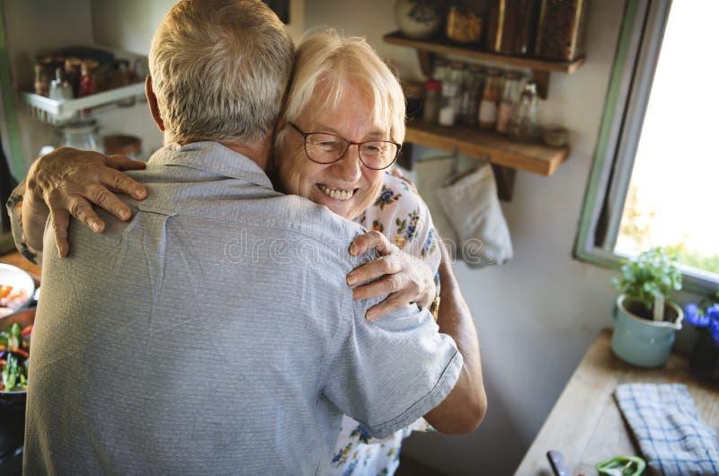 Starszy pary przytulenie w kuchni zdjęcie royalty free