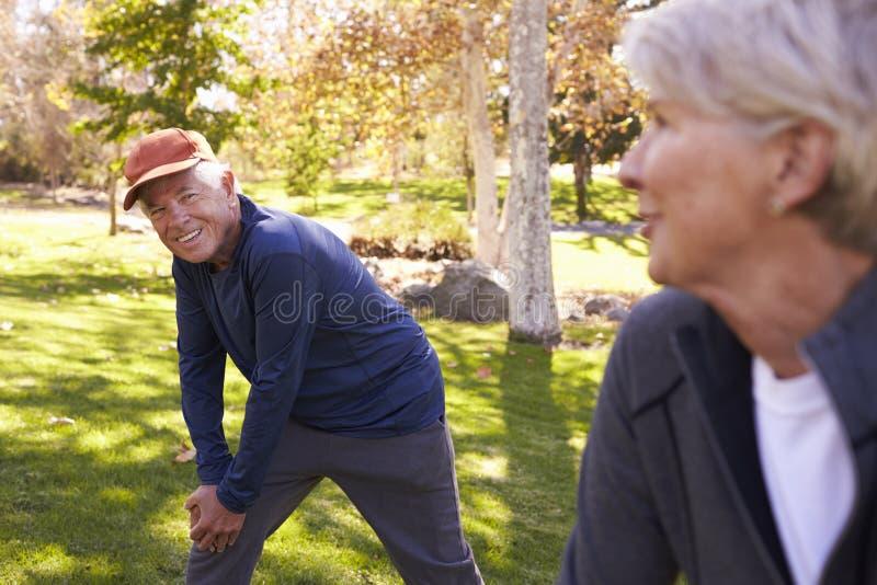 Starszy pary rozciąganie Podczas gdy Ćwiczący Wpólnie W parku obraz royalty free