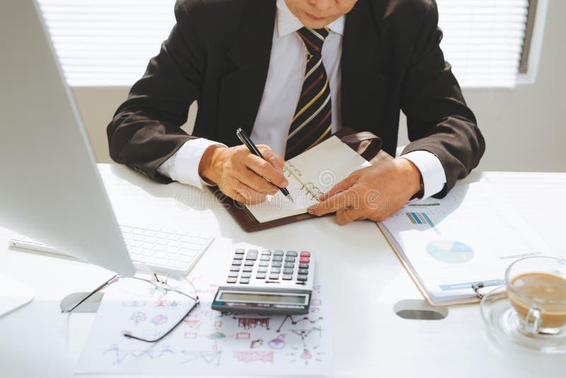 Starszy pieniężny azjatykci biznesmena obsiadanie przy jego stacją roboczą wewnątrz obraz stock