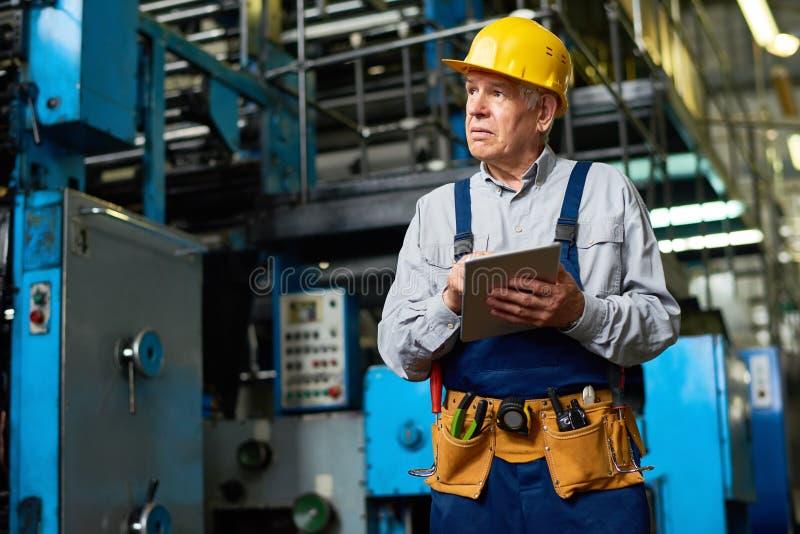 Starszy pracownik fabryczny Używa pastylkę obraz stock