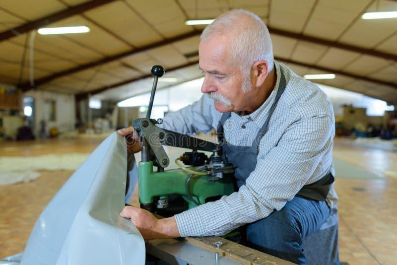Starszy pracownik w fabryce na maszynie zdjęcia royalty free