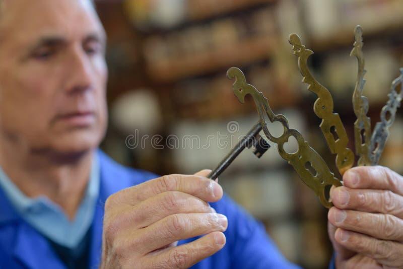 Starszy profesjonalista z różnymi typ wpisuje w locksmith obrazy royalty free