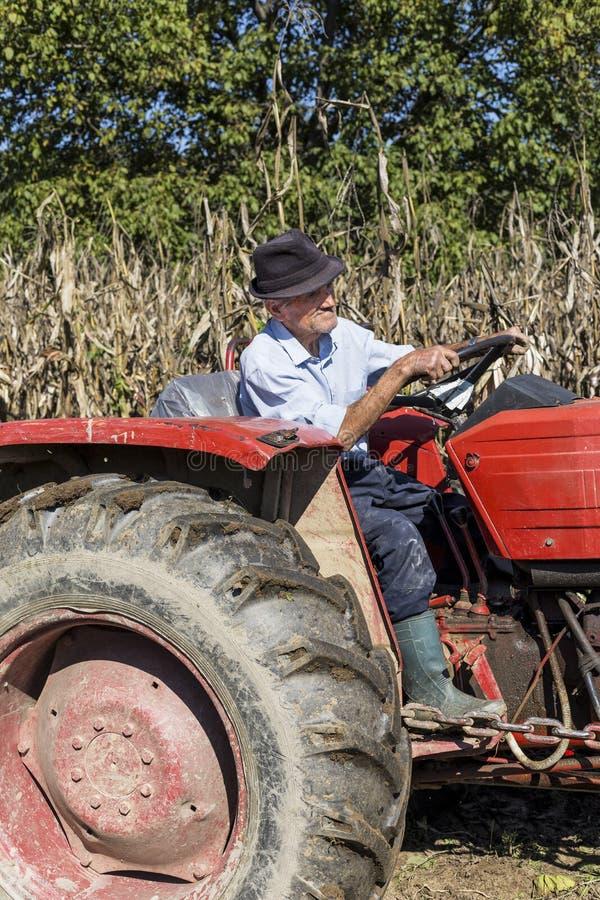 Starszy rolnik używa starego ciągnika orać jego gruntowego zdjęcia stock