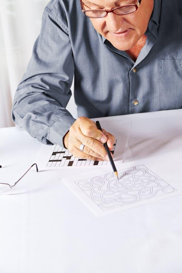 Starszy rozwiązuje rzeszoto w spoczynkowym domu obraz stock