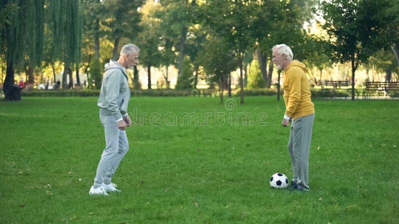 Starszy sportowowie bawi? si? futbol na weekendzie w parku, aktywny czas wolny, przyja?? zdjęcie stock