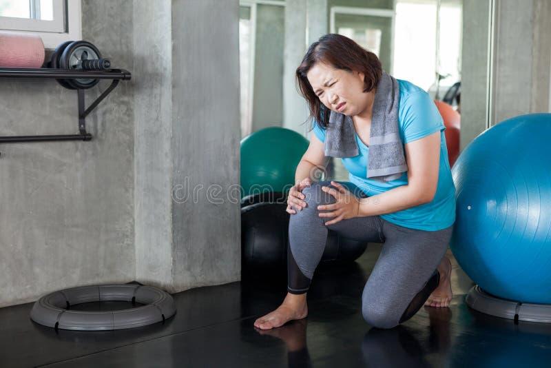 Starszy sprawności fizycznej kobiety urazu kolana ból podczas gdy ćwiczący w gym starzejący się damy cierpienie od artretyzmu Sta obrazy royalty free
