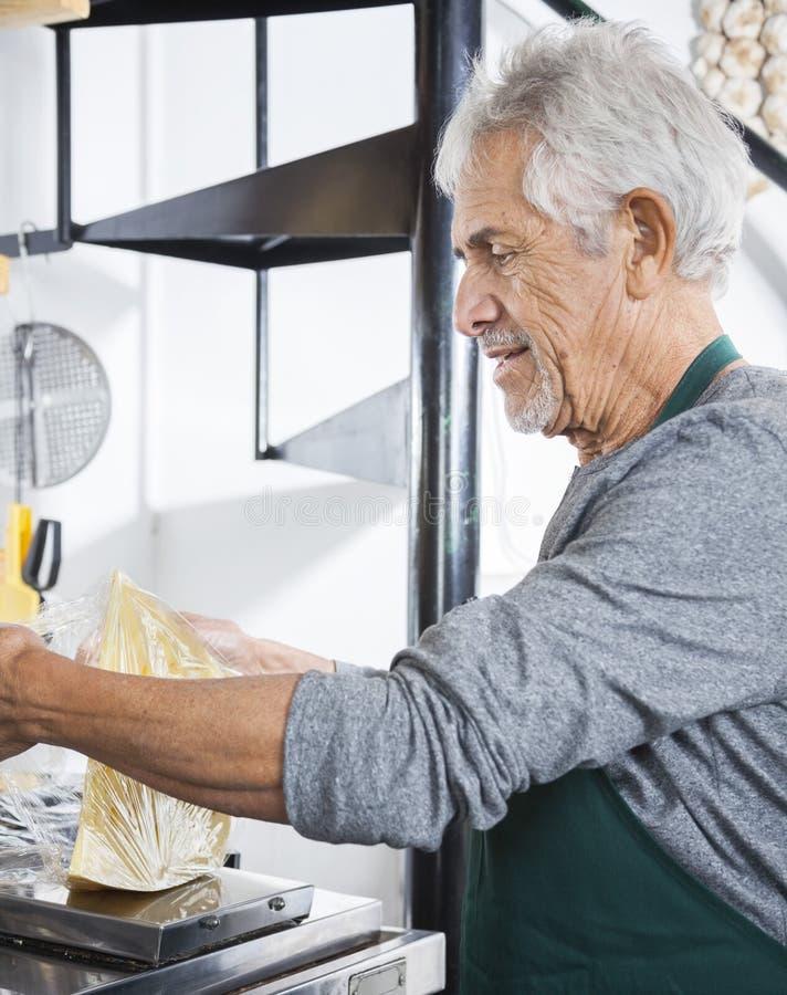 Starszy sprzedawcy kocowania ser Przy sklepem spożywczym zdjęcia royalty free