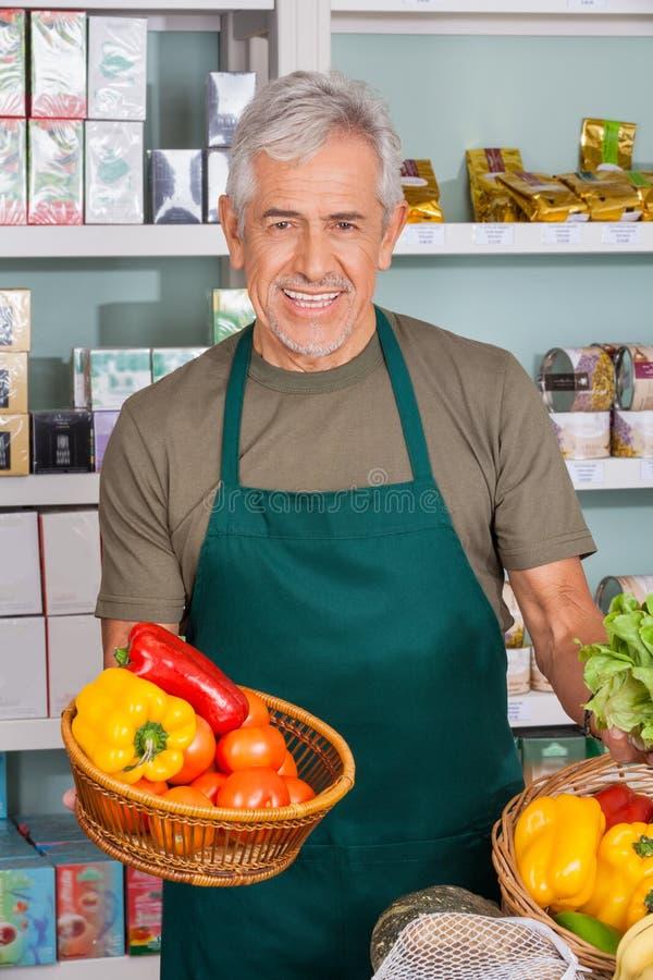 Starszy sprzedawcy mienia warzywa kosz zdjęcia stock