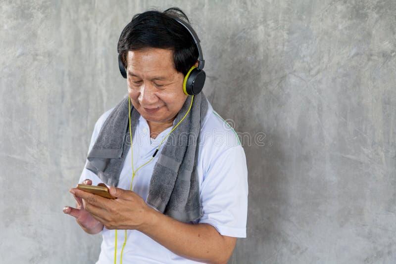 Starszy stary mężczyzna bierze przerwę od trening słuchającej muzyki z hełmofonami i telefonem relaksuje w gym aged samiec stara  obraz stock