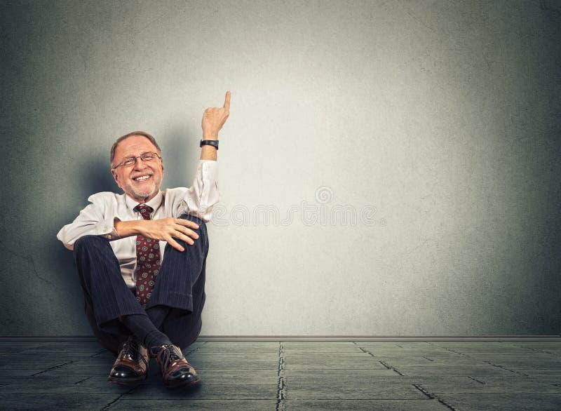 Starszy szczęśliwy mężczyzna obsiadanie na podłoga z nogami krzyżować i wskazują up obrazy stock