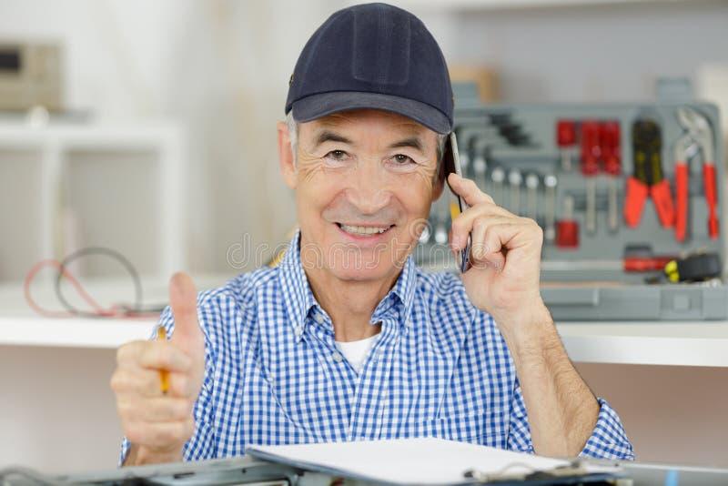 Starszy technik opowiada na telefonie z aprobata znakiem zdjęcia royalty free