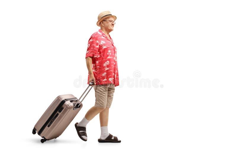 Starszy turystyczny odprowadzenie i ciągnięcie walizka zdjęcia royalty free