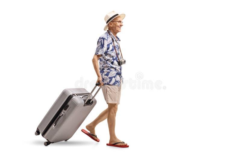 Starszy turystyczny odprowadzenie i dolezienie walizka zdjęcia stock