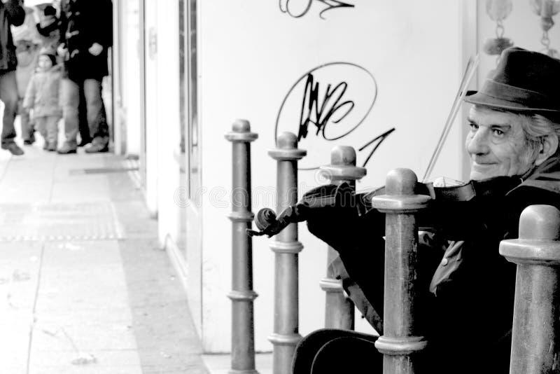Starszy uśmiechnięty uliczny muzyk bawić się skrzypki w Frankfurt, Niemcy zdjęcie royalty free