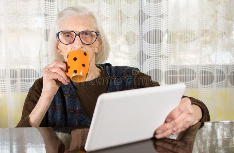 Starszy używa pastylka przyrząd w domu obrazy royalty free