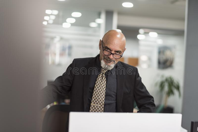 Starszy ?ysy m??czyzna pracuje w biurze z czarnym kostiumem obrazy stock