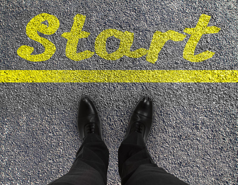 Start. Pair of feet on a tarmac road with yellow print of word start royalty free stock images