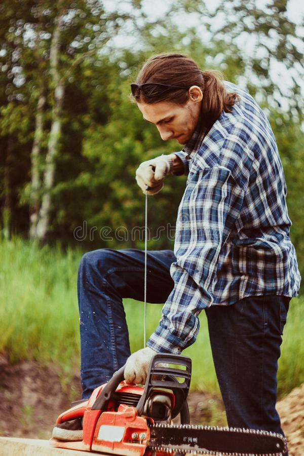 Start the chainsaw. The logger in a red checkered shirt is holding an chainsaw is going to start it, against the forest stock image