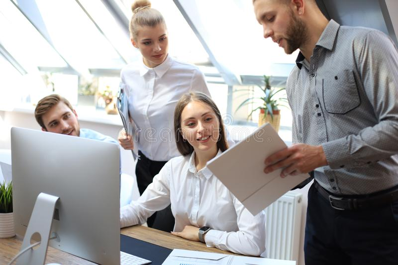 Start commercieel team op vergadering die in moderne heldere bureau binnenlandse brainstorming, aan tablet en PC-computers werken stock afbeeldingen